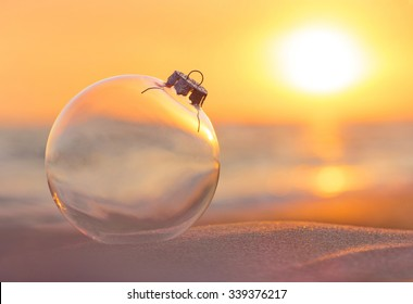 Christmas-tree decoration glass ball at sunset time ocean beach - xmas and New Year's vacation in hot countries concept