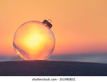 Christmas-tree decoration transparent glass ball at sunset time ocean beach - xmas and New Year vacation in hot countries concept