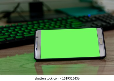 chroma key smartphone green screen placed on a computer desk background