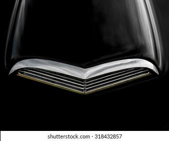 Chrome air scoop on hood of black automobile.