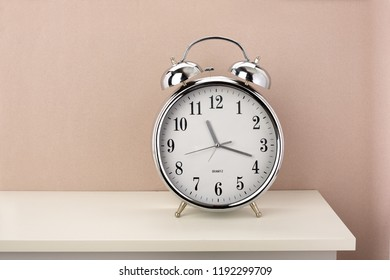 Chrome classic alarm clock on white nightstand and colored wallpaper
