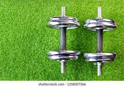 Chrome dumbbells on artificial turf