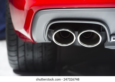 Chrome exhaust pipe of red powerful sport car bumper
