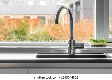 Chrome faucet by a kitchen sink with a wet window in the background