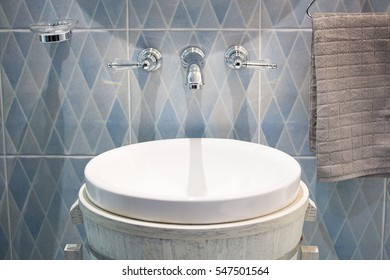 Chrome Faucet in modern bathroom with wooden bucket wash basin.
