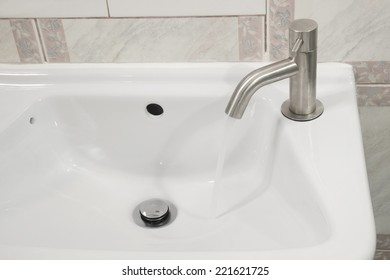 Chrome faucet on ceramic washbowl with running water.