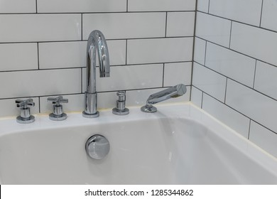 Chrome faucet with two regulators and shower head on the bath