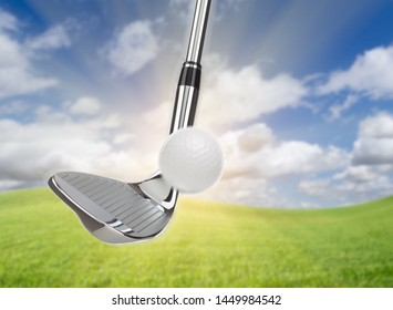 Chrome Golf Club Wedge Iron Hitting Golf Ball Against Grass and Blue Sky Background.