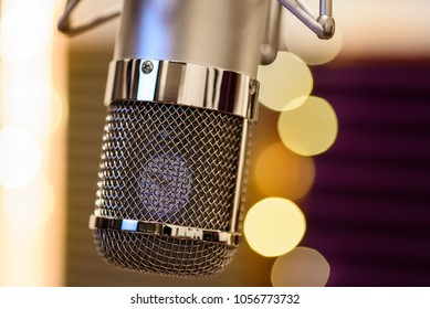 Chrome grilled recording studio tube microphone in shallow depth of field