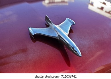 A chrome hood ornament graces the shiny red paint job on the front of a vintage American car in Miami Beach, Florida.