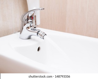 Chrome mixer tap with water in a bathroom. The photo is taken in horizontal composition.