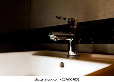 chrome plated faucet closed in a dark bathroom
