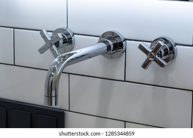Chrome plated faucet with two knobs sticking out of the wall