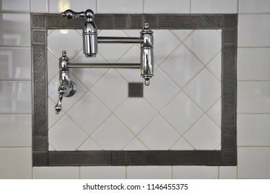 Chrome pot filler on decorative tile
