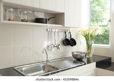 Chrome pots, pans and utensils hanging in contemporary kitchen.