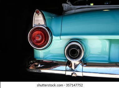 Chrome rear tail lights, bumper and exhaust of convertible turquoise Thunderbird vintage car.