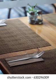 chrome stainless steel silver colour fork on wooden table top with hand crafted decoration mat prepare for guest in vintage style restaurant under natural windows lighting warm welcome mood background