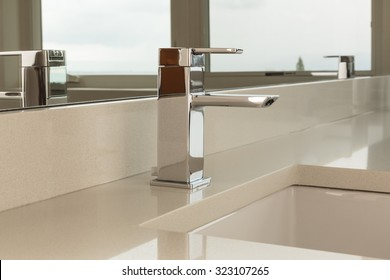 Chrome water faucet with marble counter tops and a white sink