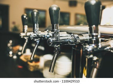 Chromed taps for draft beer in a modern bar. Beer machine detail, beer dispenser, close-up, selective focus, retro style