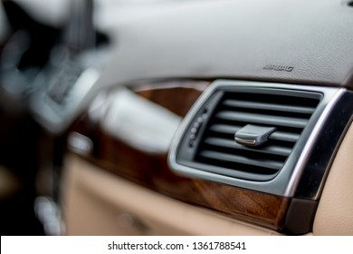 Chromed ventilation hood inside a luxury German car. Mahogany ornaments, brown board detail detail with bokeh effect. Close up photo - sharp