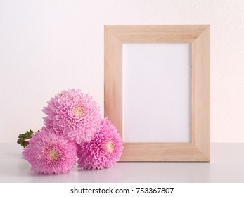 Chrysanthemum flowers and blank photo frame on table in front of