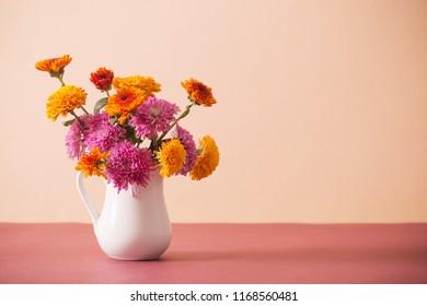 chrysanthemum flowers in white jug on pink background