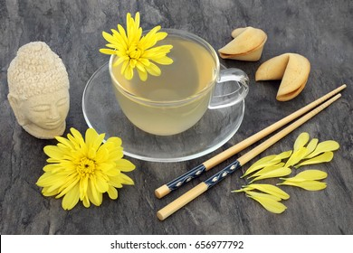 Chrysanthemum herb flower tea with glass cup, fortune cookies, chopsticks and stone Buddha head. Also used in traditional Chinese and Japanese herbal medicine.