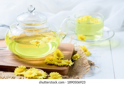 Chrysanthemum kettle and hot chrysanthemum in a mug on wood plate and white wood background, Healthy beverage for drink. Herbs and medical concept.