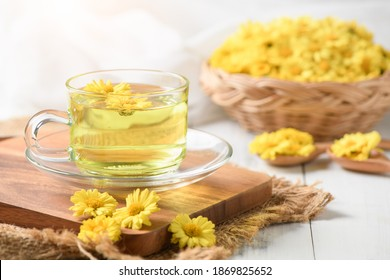 Chrysanthemum tea and Chrysanthemum flower in basket on white wood background. Healthy beverage for drink. Herbs and medical concept.