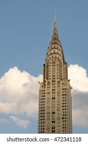 The Chrysler Building against a blue sky with with fluffy white clouds on August 8th, 2016 in New York City.