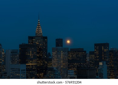 The Chrysler Building in New York City at sunset with a full moon rising in the background during the winter