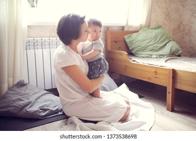 chubby baby 10 months hugging with mom, mom comforts baby, lifestyle in a regular apartment