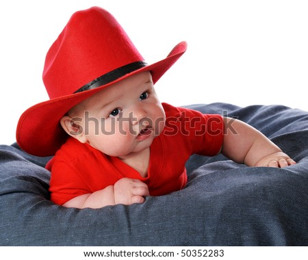 A chubby baby boy in a red cowboy hat and shirt propped on a blue beanbag 579e8fcf1e5