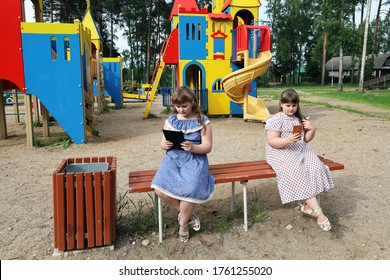 Chubby children are sitting on a bench on the playground. They are busy with their devices and do not play outdoor games. The problem of overweight in children and dependence on electronic devices