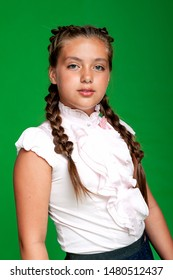 Chubby girl with braids in an elegant blouse on a green background. School clothes