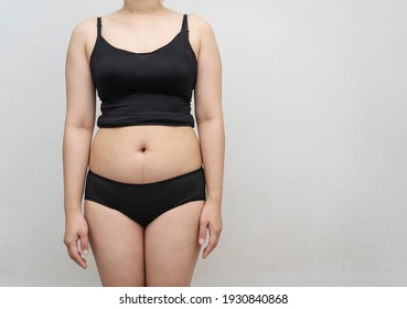 Chubby girl or fat young woman in bra  her stomach, overweight or obesity on gray background. ,Beauty, shape, healthy and health care female concept. MidSection Of  Woman With Excessive Belly Fat