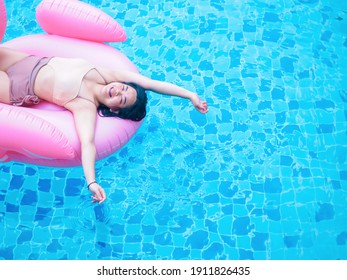 Chubby happy young woman dressed in swimsuit with inflatable flamingo in blue swimming pool.