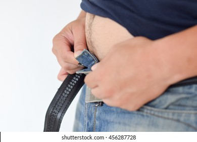 chubby man cannot button up his jean pant.Healthy and lose weight concept