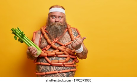 Chubby man holds celery, fights against obesity, points thumb away on copy space, has temptation for eatting sausages, keeps low carb diet, forbidden to eat junk food. Nutrition, unhealthy lifestyle
