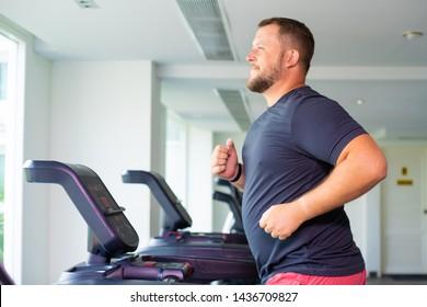 chubby man walking on running track, warming up on gym treadmill