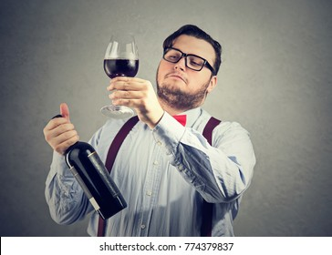 Chubby man in wearing eyeglasses and bow tie holding wineglass and judging drink quality looking overconfident.