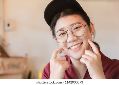 Chubby plump teen cute white tooth smile Asian young student with glasses and hat finger touch cheek with copy space