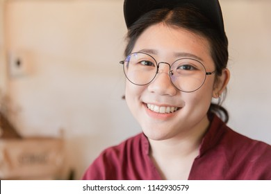 Chubby plump teen cute white tooth smile Asian young student with glasses and hat.