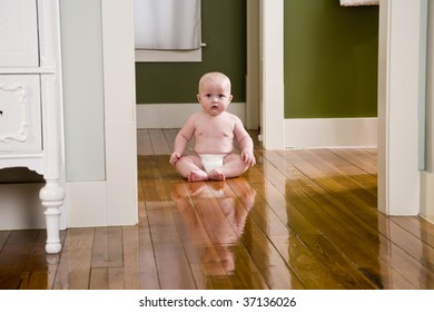 Chubby seven month old baby at home sitting on wood floor