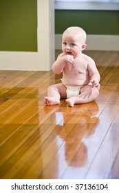 Chubby seven month old baby sitting on floor wearing diaper
