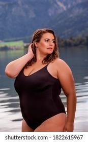 Chubby-Frau mit blondem Haar in einem schwarzen Badeanzug