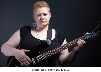 Chubby woman with short hair holding electric guitar