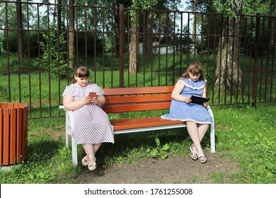 Chubby young girls are sitting on a park bench at a social distance. They are busy with their devices and do not communicate with each other. The problem of excess weight in children after quarantine