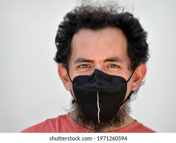CHUBURNA, YUCATAN, MEXICO - MARCH 25, 2021: Positive local likeable Mexican man with curly hair and high forehead wears a black cloth mask during the global coronavirus pandemic, on March 25, 2021.