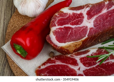 Chuck steak with rosemary, pepper and garlik on wood background